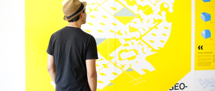 student wearing a hat looking at graphic design on a wall at UCLA